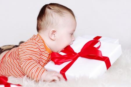 uitpakken: De baby probeert om uit te pakken een gift Stockfoto