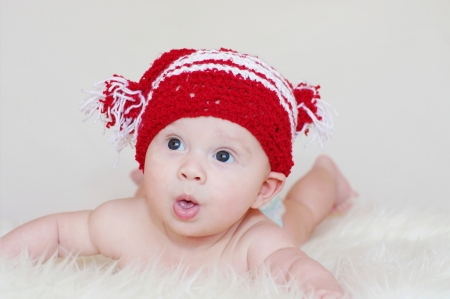 The surprised baby in a red knitted hat photo