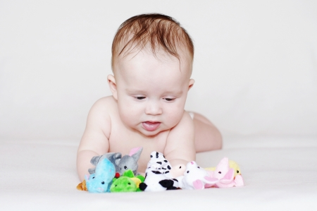 The baby plays small plush toys  4,5 months  Stock Photo