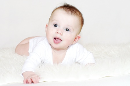 The ridiculous baby lies on a stomach on a fur rug Stock Photo - 17927487