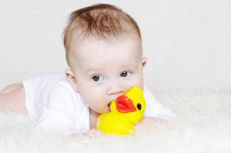 The baby gnaws a rubber duckling