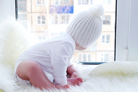 The baby in a white hat sits on a window sill photo