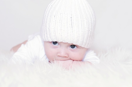 The sad baby in a white knitted hat photo