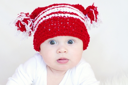 Portrait of the surprised baby in red knitted hat  photo