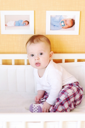 Five-months baby sits in white bed photo