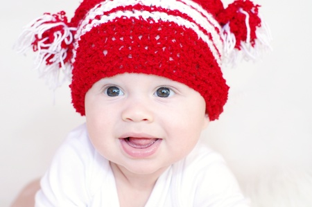 amused: Portrait of the smiling baby in a red knitted hat Stock Photo