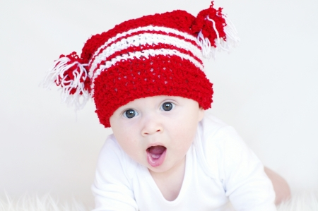 Portrait of the yawning baby in a red knitted hat photo