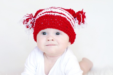 Portrait of the funny baby in red knitted hat photo