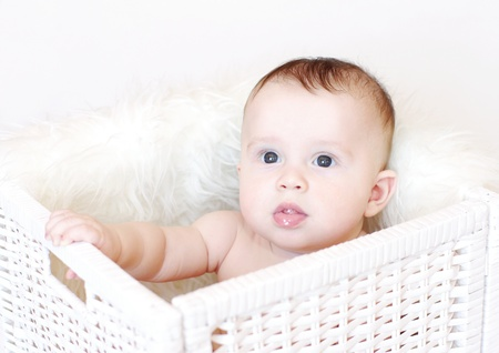 The baby sits in white basket
