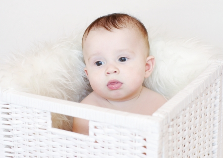 Sad baby sits in white basket photo