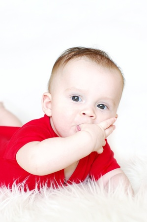 Thoughtful six-months baby holds fingers in mouth