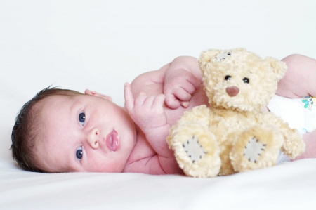 The newborn lies near a toy bear cub
