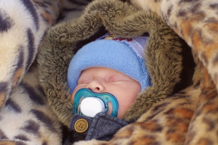 warmly: Portrait of the sleeping warmly dressed newborn with dummy Stock Photo