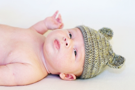 The newborn in a gray knitted hat photo