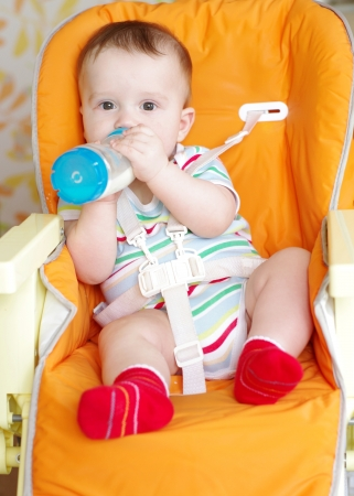 baby with feeding-bottle sitting on highchair Stock Photo