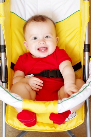 smiling baby in a yellow baby carriage  Stock Photo
