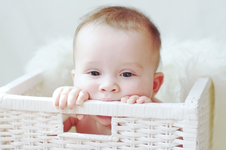 sad baby in white basket Stock Photo