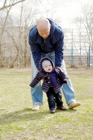 father learns his little son to go outdoors in spring Stock Photo