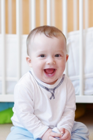 happy smiling baby against white bed  Stock Photo