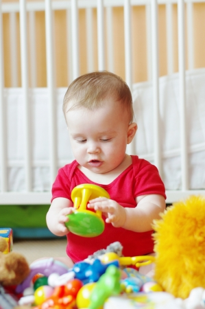 baby plays rattle against white bed  Stock Photo