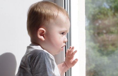 baby age of 8 months looks out of window