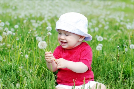 smiling baby with blowball