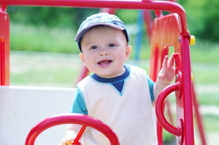happy baby plays on playground outdoors  Stock Photo
