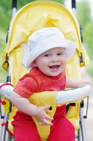 happy baby age of 9 months on baby carriage