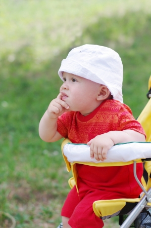 thoughtful baby age of 9 months on baby carriage photo