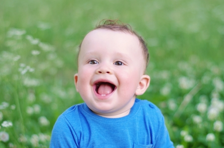 portrait of happy smiling baby age of 9 months outdoors  photo