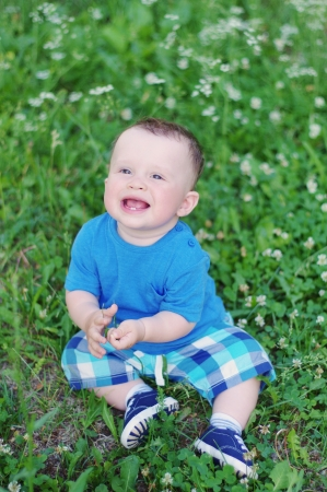 portrait of happy baby sitting on the meadow photo