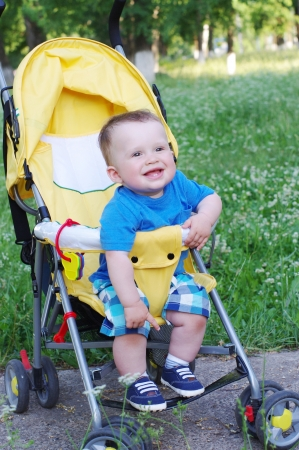 happy baby age of 9 months on baby carriage photo