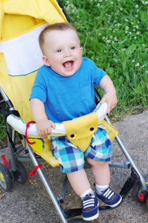 happy baby boy on yellow baby carriage
