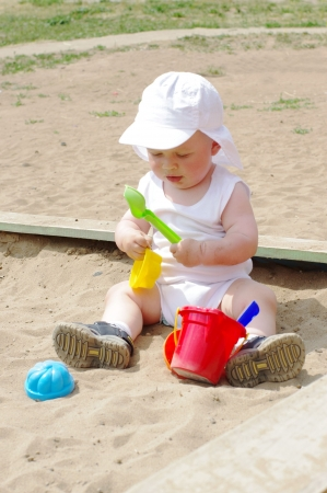 baby age of 9 months plays in sandpit Stock Photo