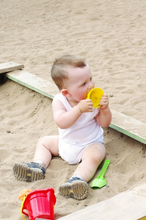 sand mold: baby plays with sand mold on playground