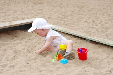 baby age of 9 months plays with sand on playground