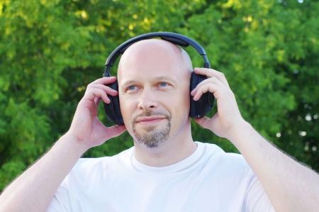 happy man listening music outdoors in wireless headset