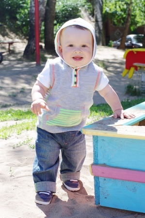 sand mold: baby age of 9 month toddles outdoors on playground Stock Photo