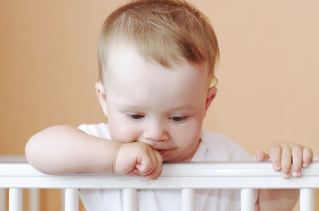 grieved: thoughtful baby in white bed