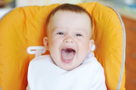 baby on chair: laughing baby in bib sits on baby chair