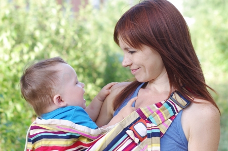 Mother carrys little son in baby sling Stock Photo