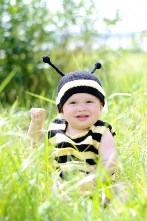 10 month: happy baby in bee costume outdoors Stock Photo