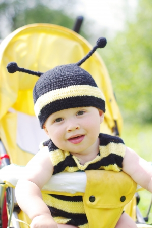 10 month: funny baby in bee costume on baby carriage