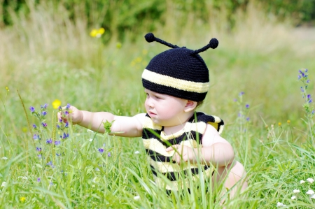baby in bee costume reaches for a flower