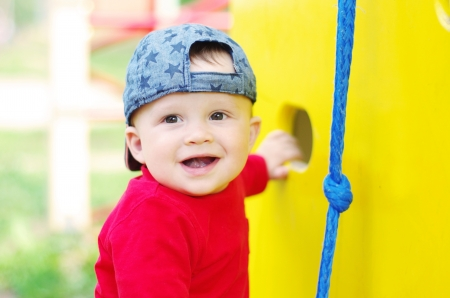 happy baby boy on playground in summertime Stock Photo