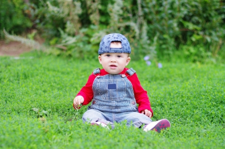 10 month: lovely baby age of 10 months  sitting on grass in park Stock Photo