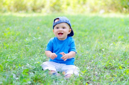 smiling baby age of 10 months sitting on grass