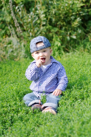 smiling baby sitting on grass in summer Stock Photo