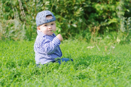 lovely baby boy sitting on grass in park