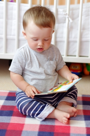 10 month: baby with book at home Stock Photo